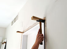Carpenter placing a new door in the reform of the house Royalty Free Stock Images