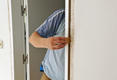 Carpenter placing a new door in the reform of the house Royalty Free Stock Photography