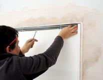 Carpenter placing a sliding door Stock Photography
