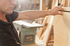 Carpenter placing a wooden flap Royalty Free Stock Images