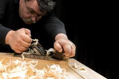 Carpenter planed board using planer Royalty Free Stock Photos