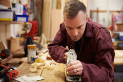 Carpenter Planing Wood In Workshop Royalty Free Stock Photo