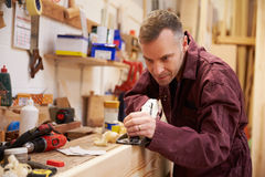 Carpenter Planing Wood In Workshop Stock Photo