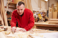 Carpenter Planing Wood In Workshop Royalty Free Stock Photography