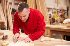 Carpenter Planing Wood In Workshop Royalty Free Stock Photos