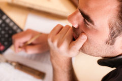 Carpenter planning his work. Man thinking with set of tools, pencil, calculator and blueprint Stock Image