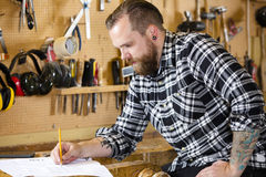 Carpenter planning new work in the workshop Stock Photo