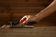 Carpenter planning wood planer tool man hand Royalty Free Stock Image