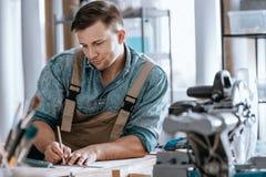 Carpenter planning work in workshop royalty free stock images