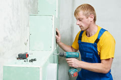 Carpenter with plasterboard and screwdriver. Carpenter joiner plasterer with screwdriver mounting gypsum plasterboard system at toilet Royalty Free Stock Photos