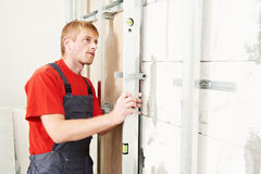 Carpenter with plasterboard and screwdriver. Carpenter joiner plasterer with screwdriver mounting gypsum plasterboard framework system on wall Stock Photos