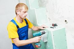 Carpenter with plasterboard and screwdriver. Carpenter joiner plasterer with screwdriver mounting gypsum plasterboard system at toilet Royalty Free Stock Photo