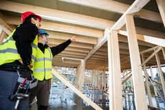 Carpenter Pointing At Roof While Standing By Colleague Royalty Free Stock Photos