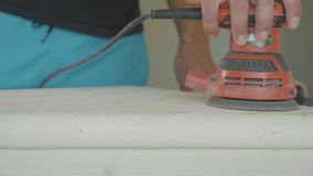 Carpenter polishing a wooden step of stairs with an electric sander, closeup stock video
