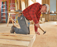 Carpenter pounding nail into interior wall. Carpenter hammering nail into bottom plate of interior wall frame royalty free stock image