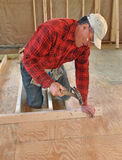Carpenter pounding nail into interior wall Royalty Free Stock Photography