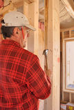 Carpenter pounding nail into interior wall. Carpenter pounding nail into stub of interior wall stock images