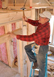 Carpenter pounding nail into interior wall. Carpenter on ladder pounding nail into interior wall stock photo