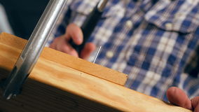 Carpenter Pounds Nail With Hammer in Workshop (Low Royalty Free Stock Photography