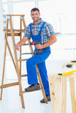 Carpenter with power drill climbing ladder at construction site Stock Image