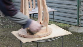 Carpenter is preparing stool for varnishing. Wooden stool dust cleaning. Furniture making stock video