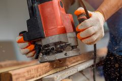 Carpenter processing furniture parts with polishing machine. Gri. Nder on board, edge processing of furniture products in side view Royalty Free Stock Image