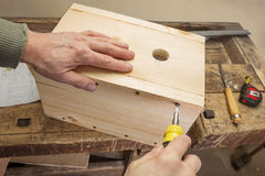 Carpenter produces birdhouse assembly in the workshop Royalty Free Stock Image
