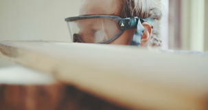 Carpenter In Protective Glasses Examining Wood stock video footage