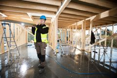 Carpenter In Protective Jacket Carrying Plank On Shoulder At Sit Stock Photo
