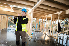 Carpenter In Protective Jacket Carrying Wood On Shoulder At Site Royalty Free Stock Photos