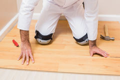 Carpenter putting down new wooden planks Royalty Free Stock Photo