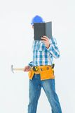 Carpenter reading book while holding hammer. Male carpenter reading book while holding hammer against white background Stock Photo