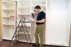 Carpenter reading scheme of cupboard installation. Stock Photos