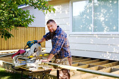 Carpenter ready to saw board. Carpenter ready to use saw to cut board stock image
