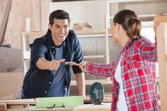 Carpenter Receiving Hammer From Female Colleague. Happy young carpenter receiving hammer from female colleague in workshop royalty free stock image