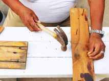 A carpenter repairing a table using a hammer and nails Royalty Free Stock Images