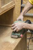 Carpenter restores vintage a sideboard by an electric of the gri Stock Image