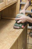 Carpenter restores vintage a sideboard by an electric of the gri Royalty Free Stock Photos