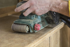 Carpenter restores vintage a sideboard by an electric of the gri Royalty Free Stock Images