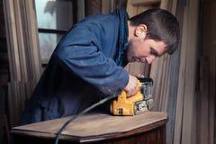 Carpenter restoring furniture with belt sander Royalty Free Stock Photography