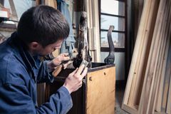 Carpenter restoring Wooden Furniture with plaster and putty Knif Stock Photo