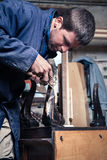 Carpenter restoring Wooden Furniture with plaster and putty Knif Royalty Free Stock Photography