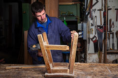 Carpenter restoring Wooden Stool Furniture in his workshop. Royalty Free Stock Photography