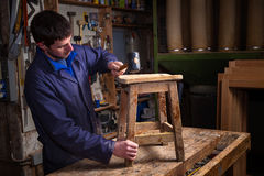 Carpenter restoring Wooden Stool Furniture in his workshop. Portrait of Carpenter wearing Blue Overalls restoring Wooden Stool Furniture in his workshop Royalty Free Stock Photos