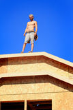Carpenter on roof. A shirtless unshaven carpenter wearing leather nail bags standing on the roof of a house that is under construction Stock Images
