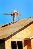 Carpenter on Roof. A carpenter wearing leather nail bags working on a roof of a house that is under construction Stock Images