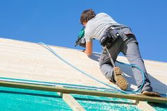 Builder at work with wooden roof construction. Carpenter roofer at work with wooden roof construction stock photos