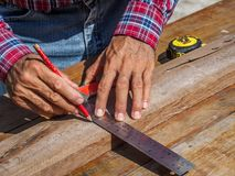 Carpenter with ruler measuring wood. profession, carpentry, wood royalty free stock photo