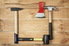 Carpenter's hammer and ax. On a wooden background Royalty Free Stock Images