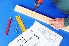 Carpenter`s hand with blueprints and drill machine Royalty Free Stock Photos
